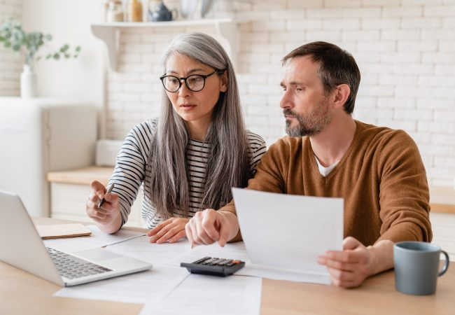 Mature middle-aged couple family wife and husband counting funds, savings declarations, investments,paperwork, financial documents, bankruptcy, court case, bills, pension with laptop.